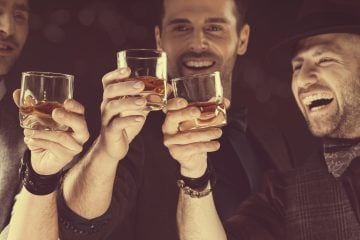 Happy friends toasting with whiskey, raising hands, laughing. Close up of hands and drinking glasses.